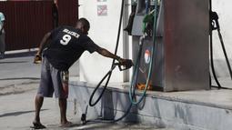 Seorang warga mencoba membakar pom bensin saat demo pemilu di Port-au-Prince, Haiti (18/1). Warga menuduh pemilu presiden Haiti berjalan curang yang menyebabkan kemarahan warga hingga membakar fasilitas umum. (REUTERS/Andres Martinez Casares)