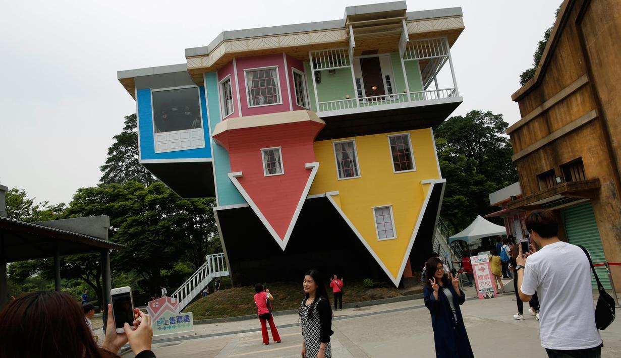Pengunjung berpose di depan rumah terbalik di Huashan Creative Park, Taipei, Taiwan, (7/4). Sekelompok arsitek Taiwan membangun rumah seluas 300 meter yang menghabiskan dana US$ 600.000 dalam kurun waktu 2 bulan. (REUTERS/Tyrone Siu)