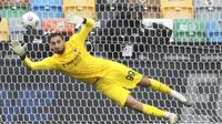 Kiper AC Milan, Gianluigi Donnarumma, berusaha menghalau bola saat melawan Udinese pada laga Liga Italia di Stadion Friuli, Minggu (1/11/2020). AC Milan menang dengan skor 2-1. (Andrea Bressanutti/LaPresse via AP)