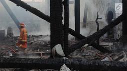 Petugas damkar melihat sisa puing kebakaran yang melanda kompleks Kelenteng Tay Kak Sie di Gang Lombok, Semarang, Kamis (21/3). Bangunan yang terbakar merupakan rumah abu yang berada satu kompleks dengan bangunan utama kelenteng. (Liputan6.com/Gholib)
