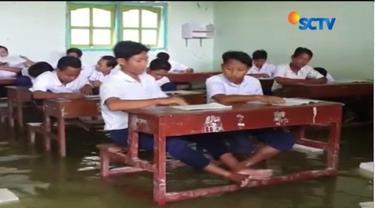 Banjir membuat para siswa yang tak mengenakan sepatu sulit berkonsentrasi saat mengisi lembar ujian karena kaki kedinginan.