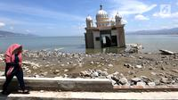 Warga melintas di depan Masjid Terapung Arqam Bab Al Rahman pasca gempa dan tsunami Palu di Pantai Talise, Sulawesi Tengah. Bangunan masjid yang terletak di pinggir pantai terlihat utuh meski sebagian bangunannya tenggelam. (Liputan6.com/Fery Padolo)