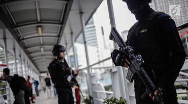 Dua anggota Brimob bersenjata lengkap berjaga di JPO kawasan Bunderan HI, Jakarta, Jumat (11/5). Penjagaan tersebut dilakukan untuk antisipasi kegiatan Aksi 115 Pembebasan Baitul Maqdis yang berpusat di Monas. (Liputan6.com/Faizal Fanani)