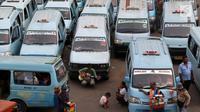 Pedagang menungu calon pembeli diantara deretan angkot di Terminal Kampung Melayu, Jakarta, Rabu (12/7). Angkot ber-AC ini merupakan bagian dari upaya untuk meningkatkan pelayanan angkutan umum kepada masyarakat. (Liputan6.com/Immanuel Antonius)