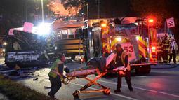 Petugas medis mengevakuasi korban tabrakan antara bus komuter dengan bus sekolah di Baltimore, Maryland, Selasa (1/11). Bus sekolah tanpa penumpang itu menabrak bagian depan bus komuter. (Courtesy Jeffrey F. Bill/Baltimore Sun via REUTERS)