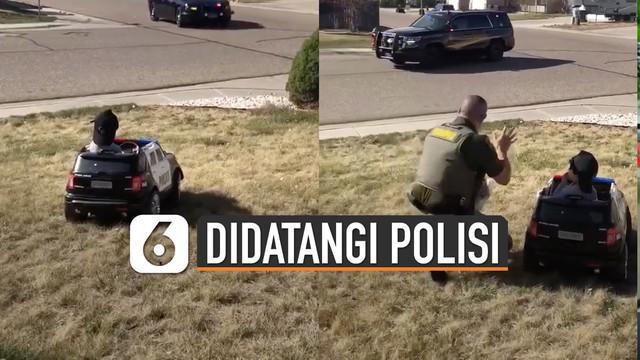 Ia yang tengah berada di balik kemudi mobil polisi mainan tampak kebingungan.