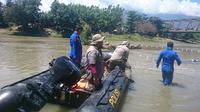Petugas gebungan sedang mengamati keberadaan buaya berkalung ban target di Sungai Palu, Sabtu (8/2/2020). (Foto: Liputan6.com/Heri Susanto)