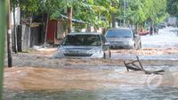 Hujan yang mengguyur Jakarta sejak Minggu (8/2) lalu, membuat Waduk Ria Rio meluap. Tampak 2 buah kendaraan menerobos banjir di kawasan Perumahan Pulomas, Jakarta, Selasa (10/2/2015). (Liputan6.com/Herman Zakharia)