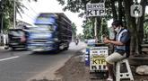 Feri (28) saat menyelesaikan jasa servis kartu tanda penduduk (KTP) di Jakarta, Kamis (21/1/2021). Bermodal meja lipat, poster, dan peralatan pendukung seperti lem, korek api, serta plastik laminating, Feri membuka jasa servis kartu identitas di pinggir jalan Ibu Kota. (merdeka.com/Iqbal S. Nugroho)