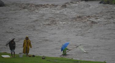 Warga Filipina menggunakan jaring mengambil material lahar dingin Gunung Mayon di sepanjang sungai di kota Daraga, provinsi Albay, Manila (27/1). Akibat hujan deras, jutaan ton abu dan batu dari gunung mayon mengalir kesungai. (AFP Photo/Ted Aljibe)
