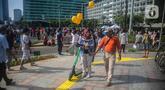 Petugas Satpol PP memberhentikan pengguna skuter listrik saat Car Free Day (CFD) di kawasan Bundaran HI, Jakarta, Minggu (17/11/2019). Dinas Perhubungan DKI Jakarta melarang penggunaan skuter listrik di kawasan CFD. (Liputan6.com/Faizal Fanani)