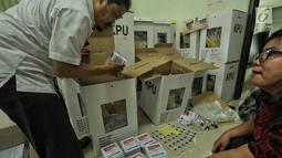 Petugas memasukkan logistik Pemilu 2019 ke kotak suara saat proses persiapan distribusi di Kecamatan Menteng, Jakarta, Senin (15/4). Proses pendistribusian ke tps masing-masing kelurahan diperkirakan akan tuntas sehari sebelum hari pencoblosan pada 17 April 2019. (Liputan6.com/Faizal Fanani)