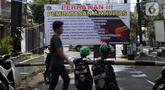 Spanduk tentang pembatasan aktivitas terpampang di pintu masuk perumahan di kawasan Cideng, Jakarta, Kamis (2/4/2020). Pemerintah menetapkan Pembatasan Sosial Berskala Besar dengan membatasi kegiatan tertentu penduduk di wilayah yang diduga terinfeksi COVID-19. (Liputan6.com/Helmi Fithriansyah)