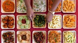 Seorang koki memajang aneka hidangan yang ditawarkan di sebuah kedai makanan dalam festival Bengaluru Aaharotsava, Bangalore, India, Jumat (18/10/2019). Lebih dari 100 kios hadir dalam Bengaluru Aaharotsava. (Manjunath Kiran/AFP)