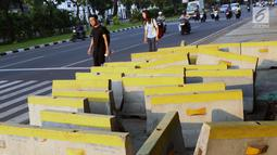 Pejalan kaki menghindari beton pembatas jalan yang diletakkan di atas trotoar Jalan Medan Merdeka Utara, Jakarta, Kamis (25/7/2019). Pembatas jalan yang berada tidak pada tempatnya mengganggu kenyamanan pejalan kaki yang melintasi trotoar jalan tersebut. (Liputan6.com/Helmi Fithriansyah)