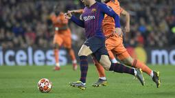 Duel Arthur dan Nabil Fekir pada leg kedua, babak 16 besar Liga Champions yang berlangsung di Stadion Camp Nou, Barcelona, Kamis (14/3). Barcelona menang 5-1 atas Lyon. (AFP/Josep Lago)