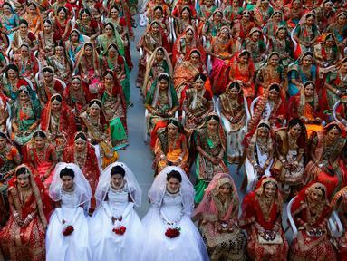 Pengantin perempuan duduk bersama saat nikah massal di Surat, India, Minggu (23/12). Nikah massal bagi perempuan yatim ini digelar oleh pengusaha berlian asal India, Mahesh Savani. (AP/Ajit Solanki)