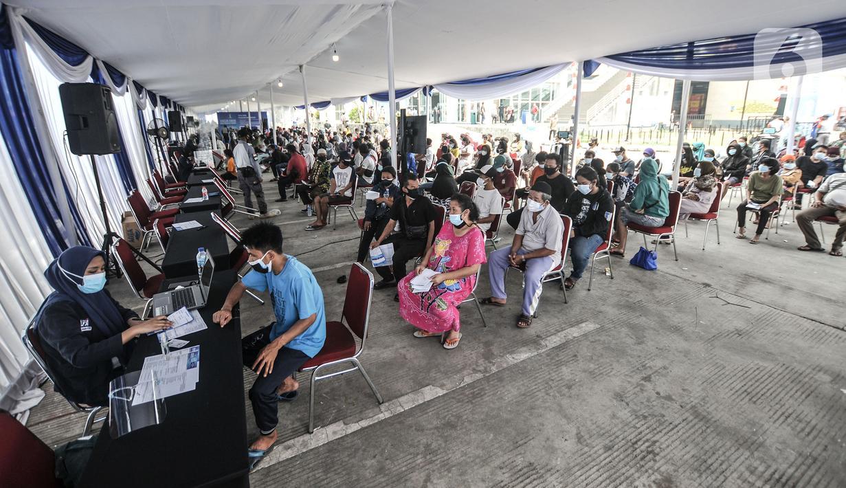 Warga antre mendaftar untuk mengikuti vaksinasi massal Covid-19 di Pasar Ikan Modern Muara Baru, Penjaringan, Jakarta, Kamis (5/8/2021). Vaksinasi massal di Pasar Ikan Muara Baru pada 5-7 Agustus ini menyasar masyarakat kawasan pesisir yang berusia 12 tahun ke atas. (merdeka.com/Iqbal S Nugroho)