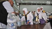 Petugas membagikan air zam-zam untuk jemaah haji Kloter 2 asal Banten di Asrama Haji Pondok Gede, Jakarta, Rabu (29/8). Setiap jemaah mendapatkan lima liter air zam-zam yang dibagikan secara cuma-cuma (Merdeka.com/ Iqbal S. Nugroho)