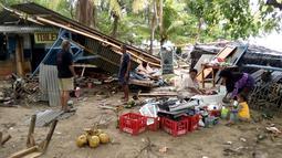 Warga mengumpulkan barang-barang dari bangunan yang rusak setelah tsunami menerjang Pantai Carita, di perairan Banten, Minggu (23/12). Tsunami menerjang pantai di Selat Sunda, khususnya di daerah Pandenglang, Lampung Selatan, dan Serang. (SEMI / AFP)
