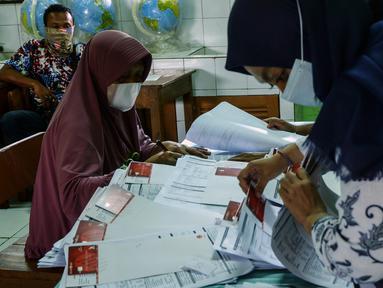 Petugas mencari data warga penerima manfaat saat pencairan bantuan sosial tunai (BST) di SDN Kembangan Utara 05 Pagi, Jakarta, Rabu (31/3/2021). Program BST sebesar Rp300 ribu dari Kemensos ini disalurkan melalui RT-RT se kelurahan Kembangan Utara melalui ATM Bank DKI. (Liputan6.com/Johan Tallo)