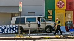 Petugas kepolisian berjalan dekat mobil van yang menabrak kerumunan orang di depan sebuah restoran di Los Angeles, Minggu (30/7). Van itu menabrak truk pickup sebelum menabrak pembatas jalan dan menghantam bagian luar resto. (AP Photo/Damian Dovarganes)
