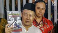 Mantan Kepala BPPN, Syafruddin Arsyad Temenggung menunjukkan buku yang ditulisnya saat meninggalkan Rutan KPK, Jakarta, Selasa (7/9/2019). Sebelumnya, Majelis Hakim Pengadilan Tipikor Jakarta menjatuhi vonis 13 tahun penjara dan denda Rp700 juta. (Liputan6.com/Helmi Fithriansyah)