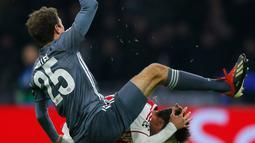 Gelandang Bayern Munchen Thomas Mueller menendang kepala bek Ajax Amsterdam Nicolas Tagliafico dalam laga Grup E Liga Champions di Amsterdam, Belanda, Rabu (12/12). Usai menendang Tagliafico, Muller menunjukkan gestur meminta maaf. (AP Photo/Peter Dejong)