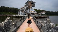 Foto pada 27 April 2019 memperlihatkan pengunjung berpose di depan bangunan berbentuk naga di Taman Air Ho Thuy Tien yang telah lama ditinggalkan di kota Hue, Vietnam. Taman air Ho Thuy Tien pertama kali dibuka untuk umum dalam keadaan setengah selesai pada tahun 2004. (Manan VATSYAYANA/AFP)