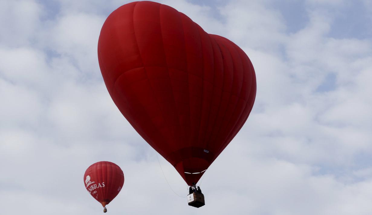 Sebuah balon udara panas berbentuk hati (kanan) terbang di langit selama Love Cup 2016 di Jekabpils, Latvia (14/2). Nikah massal yang diikuti oleh 50 pasangan ini menggelar akad di atas 27 balon udara. (REUTERS/Ints Kalnins)