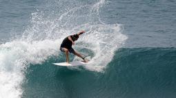 Turis beraksi di atas ombak saat bermain selancar di pantai Uluwatu Kuta Selatan di Kabupaten Badung, Bali pada 20 Desember 2018. Di Bali, terdapat banyak pantai yang merupakan lokasi ideal untuk kegiatan berselancar. (Photo by SONNY TUMBELAKA / AFP)