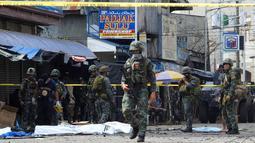 Polisi dan tentara berjaga pasca ledakan bom di Gereja Katolik Jolo, Filipina Selatan, Minggu (27/1). Bom kedua meledak di tempat parkir gereja ketika aparat setempat merespons. (Nickee Butlangan/AFP)