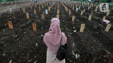 Keluarga berdoa depan pusara makam korban Covid-19 di TPU Srengseng Sawah 2, Jakarta Selatan, Jumat (19/3/2021). Seminggu terakhir intensitas pemakaman korban Covid-19 menurun drastis sebesar rata-rata 20 jenazah/minggu dibandingkan sebelumnya rata-rata 35 jenazah/minggu. (merdeka.com/Arie Basuki)