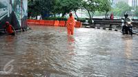 Petugas PPSU Kel Kuningan Barat mencari saluran pembuangan air di putaran kolong fly over Kapt Tendean, Jakarta, Selasa (9/2/2016). Hujan yang mengguyur Jakarta sore ini mengakibatkan putaran ini tergenang air. (Liputan6.com/Helmi Fithriansyah)