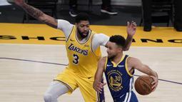 Pebasket Golden State Warriors Stephen Curry (kanan) berupaya melewati hadangan pebasket LA Lakers Anthony Davis dalam pertandingan NBA di Staples Center,  Los Angeles, California, Amerika Serikat, Senin (18/1/2020). (AP Photo/Jae C. Hong)