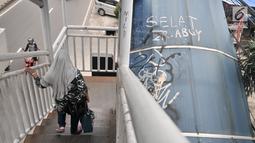Pejalan kaki melintasi JPO yang tidak terawat di JPO Imigrasi Jakarta Timur, Kamis (17/1). JPO yang berada di depan Kantor Imigrasi Jakarta Timur dalam kondisi tidak terawat, seperti atap yang sudah rusak dan penuh coretan. (Merdeka.com/Iqbal S. Nugroho)