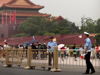 Petugas keamanan berjaga-jaga di depan Gerbang Tiananmen di sebelah Lapangan Tiananmen di Beijing (4/6/2019). Pemerintah China meningkatkan keamanan di sekitar Lapangan Tiananmen di pusat Beijing jelang peringatan tragedi Tiananmen 1989. (AP Photo/Mark Schiefelbein)