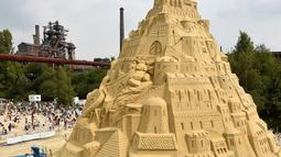 Sejumlah seniman saat menyelesaikan istana pasir di Landschaftspark di Duisburg, Jerman , (1/9). Seniman dari Duisburg burusaha meraih Guinness Book of World Records dengan membuat istana pasir tertinggi yang pernah ada. (Marcel Kusch / dpa via AP)