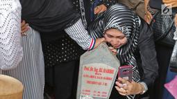 Seorang wanita berswafoto dengan batu nisan Presiden ketiga BJ Habibie di Taman Makam Pahlawan Nasional Kalibata, Jakarta, Kamis (12/9/2019). Selain berdoa, tidak sedikit juga warga  mengabadikan dengan kamera ponsel. (Liputan6.com/Herman Zakharia)