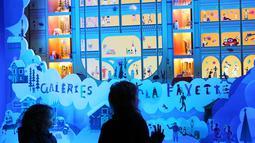 Anak-anak yang melintas berhenti untuk melihat etalase Natal di pusat perbelanjaan Galeries Lafayette di Paris, Prancis, pada 22 November 2020. Deretan pusat perbelanjaan telah meluncurkan etalase Natal mereka meskipun masih tutup selama karantina wilayah kedua di seluruh Prancis. (Xinhua/Gao Jing)