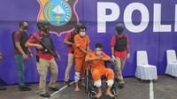 Dua tersangka pembunuhan pengusaha sewa mobil setelah tertangkap Polda Riau. (Liputan6.com/M Syukur)