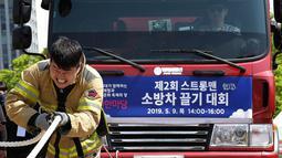Ekspresi petugas pemadam kebakaran Lim Sung-joo saat menarik sebuah truk pemadam kebakaran dengan seutas tali dalam acara Safe Seoul Festival di Seoul, Korea Selatan, Kamis (9/5/2019). Safe Seoul Festival ditujukan bagi anak-anak dan keluarga. (AP Photo/Ahn Young-joon)