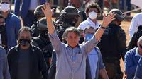 Presiden Brasil Jair Bolsonaro (tengah) melambaian tangan kepada pendukungnya saat peresmian rumah sakit lapangan di Aguas Lindas, Goiais, Brasil, 5 Juni 2020. Hingga 6 Juli 2020, otoritas Brasil melaporkan 1,6 juta orang dinyatakan positif dan 65 ribu di antaranya meninggal dunia. (Sergio LIMA/AFP)