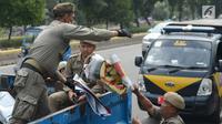 Petugas Satpol PP menertibkan APK Pemilu 2019 di Kawasan Jalan Pemuda, Jakarta, Rabu (13/3). APK Pemilu 2019 yang terpasang pada JPO dibersihkan hal tersebut mengganggu dan melanggar aturan pemasangan dari komisi Pemilihan umum. (merdeka.com/Imam Buhori)