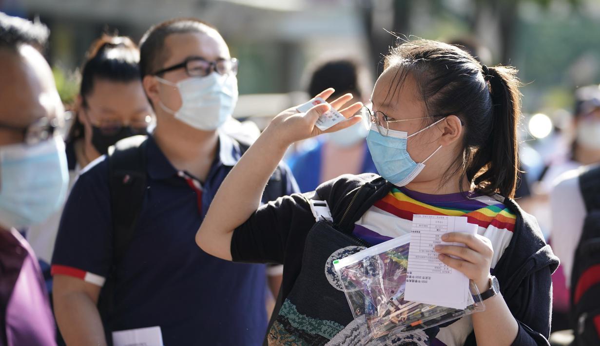 Seorang peserta bersiap memasuki lokasi ujian masuk perguruan tinggi di Sekolah Menengah Atas No. 8 Beijing di Beijing, ibu kota China (7/7/2020). Ujian masuk perguruan tinggi nasional China tahun ini telah dimulai pada Selasa (7/7). (Xinhua/Xing Guangli)