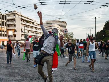 Pengunjuk rasa melempar batu ke kedutaan Israel pada unjuk rasa di Athena, Yunani, Selasa (15/5). Mereka mengecam tentara Israel menembak mati puluhan warga Palestina di perbatasan Gaza yang berunjuk rasa menentang pembukaan kedubes AS (AFP/Aris MESSINIS)