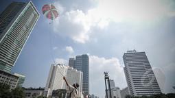 Imron (65) menerbangkan parasut mainan jualannya di kawasan Bundaran HI, Jakarta, Minggu (22/3/2015).  Seiring dengan perkembangan zaman dan modernisasi, permainan tradisional kini mulai tergantikan. (Liputan6.com/Faizal Fanani)