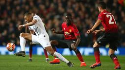Penyerang Paris Saint-Germain, Kylian Mbappe mengontrol bola dengan dibayangi pemain Manchester United pada leg pertama 16 besar Liga Champions di Stadion Old Trafford, Selasa (12/2). Manchester United berhasil dikandaskan PSG, 0-2 (AP/Dave Thompson)