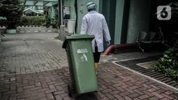 Petugas membawa tong sampah berisi limbah Covid-19 di Tempat Penyimpanan Sementara Limbah B3 di Labkesda DKI Jakarta, Selasa (4/8/2020). Pembuangan limbah Covid-19 di Labkesda DKI Jakarta dilakukan dengan proses ketat sesuai protokol kesehatan. (merdeka.com/Iqbal Nugroho)
