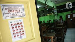 Petugas marapikan bangku di SD Negeri Kota Bambu 03/04, Jakarta, Sabtu (21/11/2020). Pemerintah pusat memberikan kewenangan pemerintah daerah membuka sekolah dan melakukan pembelajaran tatap muka pada semester genap tahun ajaran 2020/2021. (Liputan6.com/Faizal Fanani)